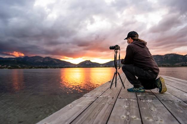 Turysta pasjonujący się fotografią pochyla się, aby ustawić aparat, aby uzyskać dobre zdjęcie