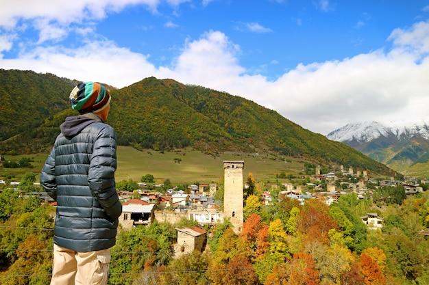 Turysta pod wrażeniem panoramicznego widoku miasta mestia z wieżą svan wśród jesiennych liści, georgia