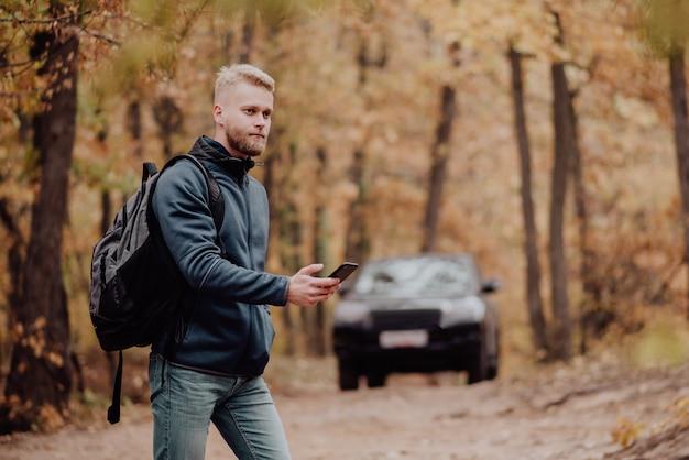 Turysta podróżuje samochodem. mężczyzna w telefonie patrzy na nawigator.