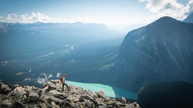 Turysta podziwiający widok na polodowcową dolinę i jezioro po zdobyciu szczytu góry