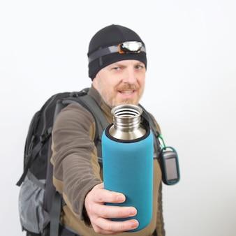 Turysta pokazuje metalową butelkę wody na białym tle
