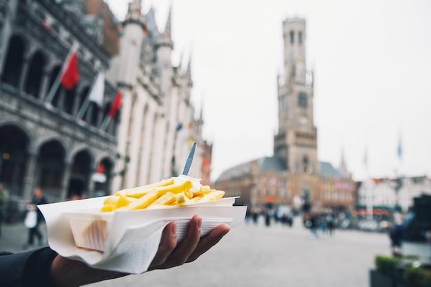 Turysta posiada popularne uliczne fast foody frytki w holandii amsterdam holandia