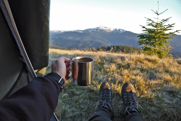 Turysta przy filiżance kawy w namiocie z widokiem na góry