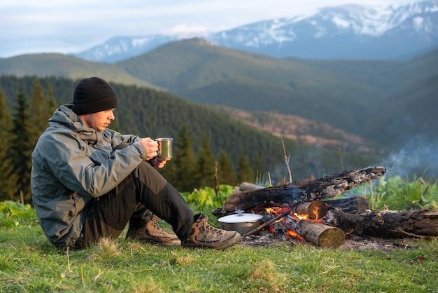 Turysta przygotowuje jedzenie na stosie podczas wędrówki po górach na wysokości