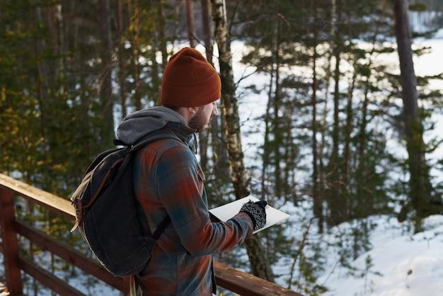 Turysta robi notatki z podróży w lesie lub rysuje szkic natury ekologicznej