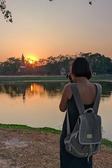 Turysta robi zdjęcia o zachodzie słońca w historycznym parku sukhothai w tajlandii