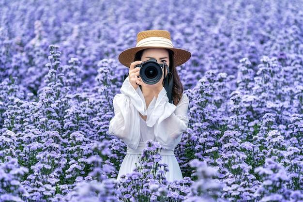 Turysta robi zdjęcie aparatem cyfrowym na polach kwiatów margaretki