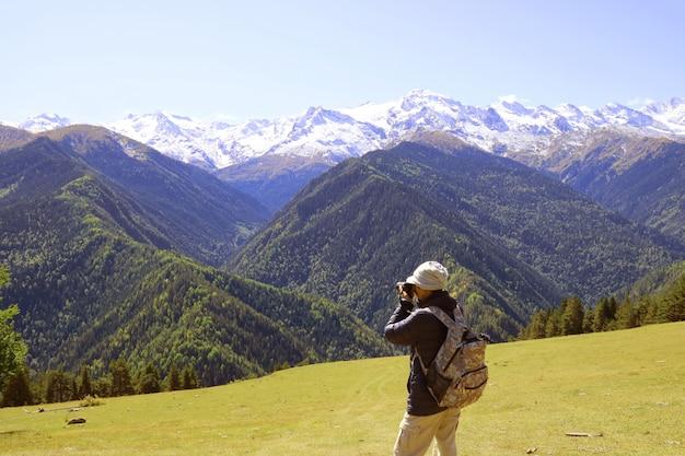 Turysta robienia niesamowitych zdjęć ośnieżonych gór kaukazu w mestii w stanie georgia