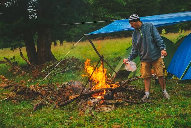 Turysta rozpala ogień w lesie w pobliżu namiotów