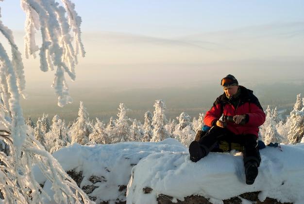 Turysta siedzący na plecaku przy skale zimą odpoczywa nalewając herbatę z termosu
