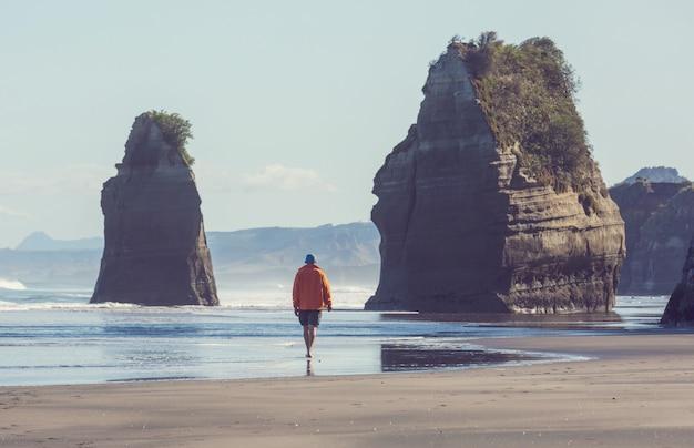 Turysta spacerujący po plaży w formacji skalnej three sisters na wybrzeżu new plymouth w nowej zelandii
