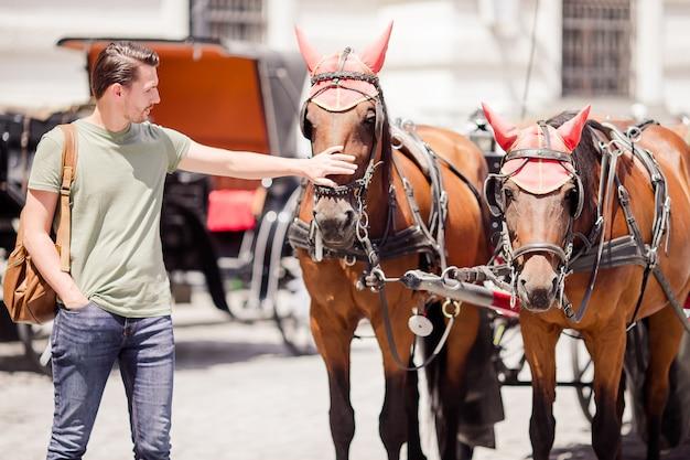 Turysta spacerujący po wiedniu i patrząc na dwa konie w powozie