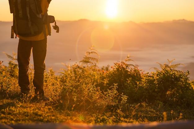Turysta stoi na kempingu w pobliżu pomarańczowego namiotu i plecaka w górach