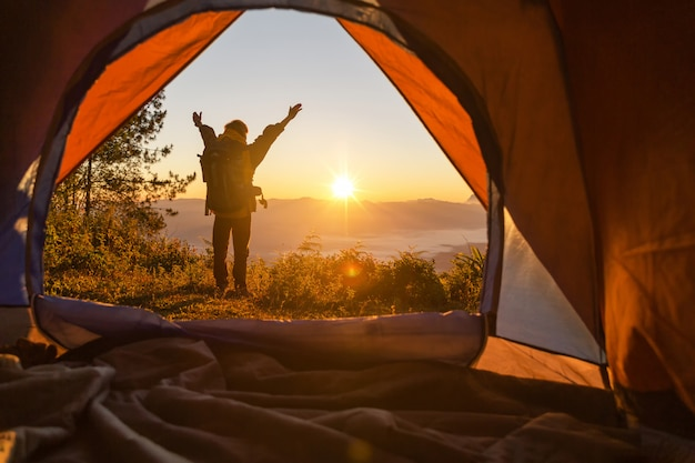 Turysta stoi na namiocie kempingowym z pomarańczowym frontem i plecaku w górach