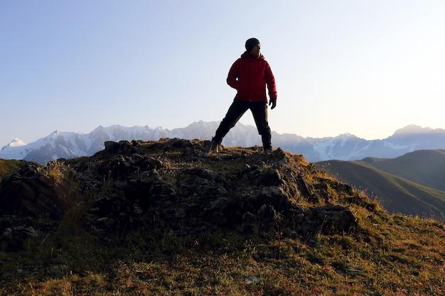 Turysta stoi na wzgórzu w górzystym terenie w gruzji