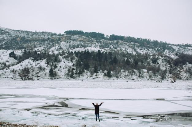 Turysta stoi z rękami na krze na tle zamarzniętej rzeki w pochmurny dzień. zimowa przygoda.
