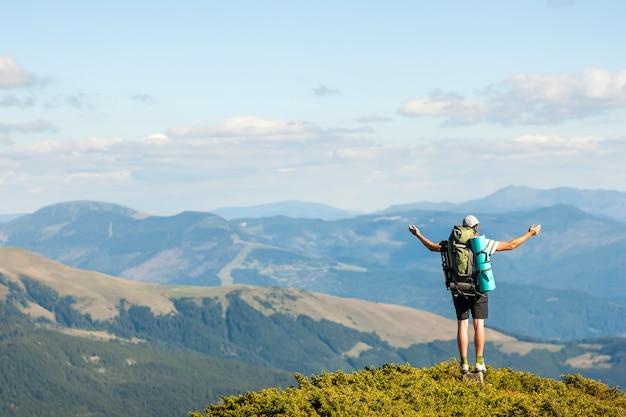 Turysta stojący na szczycie góry. jedność z naturą.