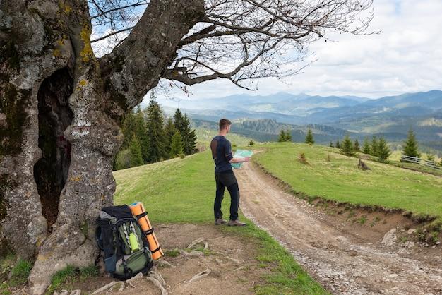 Turysta studiuje mapę okolicy siedzącej pod drzewem przy drodze