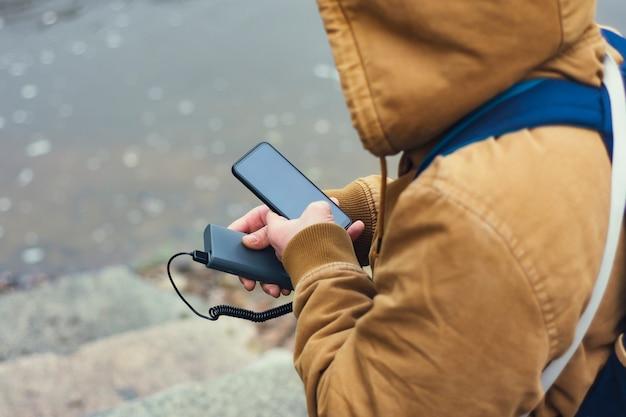 Turysta trzyma w ręku przenośną ładowarkę ze smartfonem.