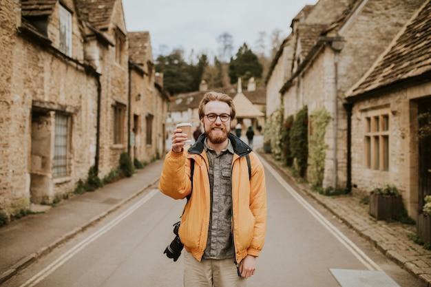 Turysta trzymający filiżankę kawy uśmiechający się w wiosce
