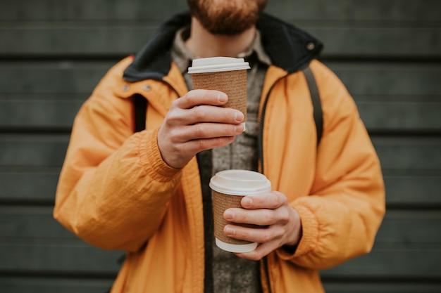 Turysta trzymający ułożone kubki z kawą