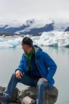 Turysta turysta patrząc na widok krajobraz góry lodowej z gigantycznymi górami lodowymi i jeziorem. charakter arktyczny silnie dotknięty zmianami klimatycznymi