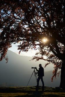 Turysta turysta z aparatem na trawiastej dolinie na górski krajobraz pod wielkim drzewem.