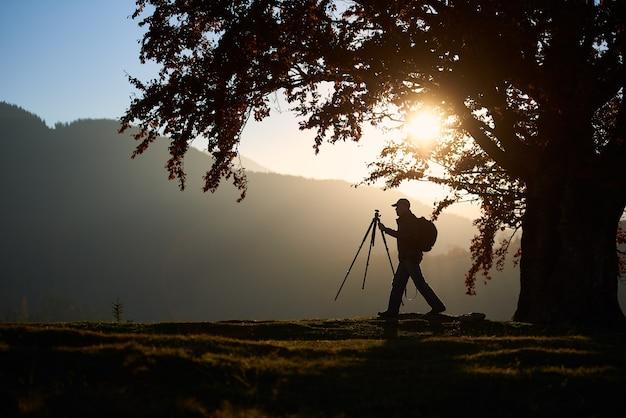 Turysta turysta z aparatem na trawiastej dolinie na tle górskiego krajobrazu pod wielkim drzewem.