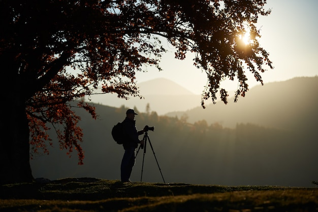 Turysta turystyczny człowiek z kamerą na trawiastej dolinie na tle górskiego krajobrazu pod wielkim drzewem.