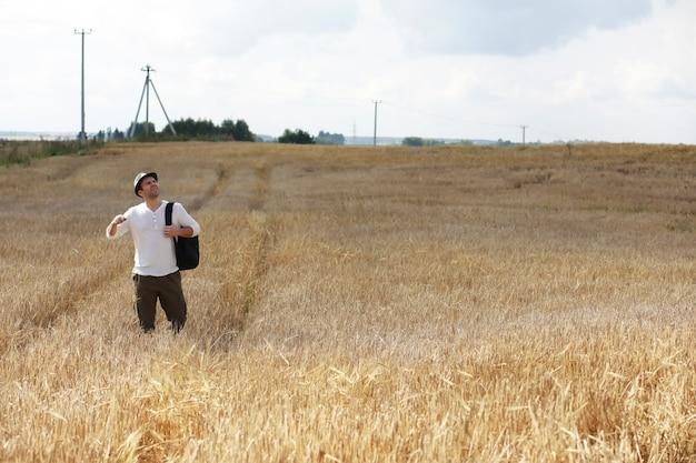 Turysta w dziedzinie roślin zbożowych. mężczyzna na polu pszenicy. zbiór zbóż.