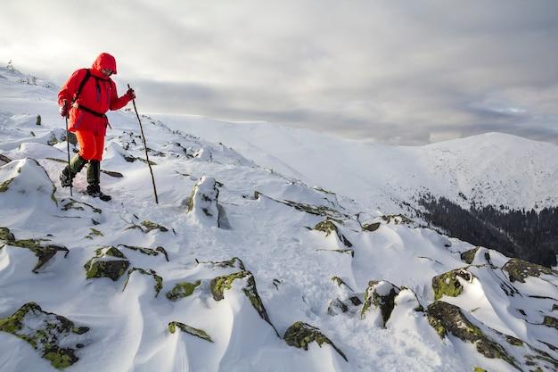 Turysta w jaskrawoczerwonym ubraniu z laskami schodzący z niebezpiecznego skalistego zbocza góry pokrytego śniegiem na burzowym pochmurnym niebie