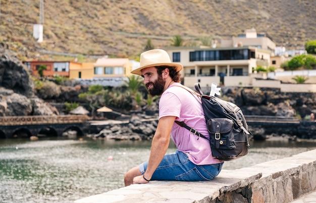 Turysta w kapeluszu i plecaku w nadmorskiej miejscowości el hierro na wyspach kanaryjskich