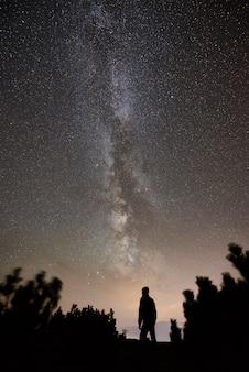 Turysta w nocy camping na szczycie góry pod gwiaździstym niebem