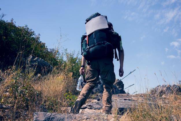 Turysta w plecaku wznosi się w górach