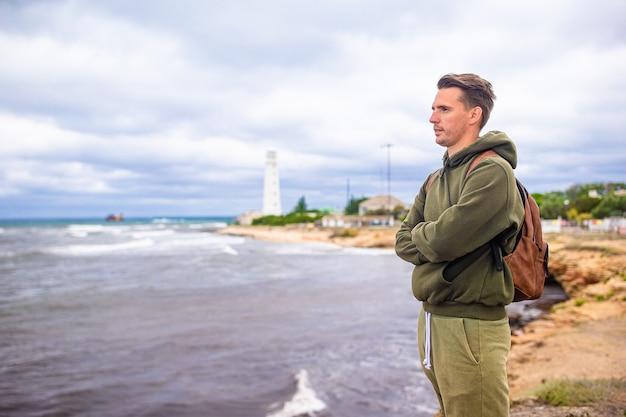 Turysta w pobliżu wybrzeża burzliwego morza spojrzeć na latarnię morską