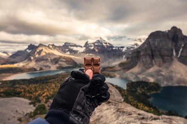 Turysta w rękawiczce trzymający kawałek czekolady na szczycie gór skalistych
