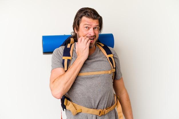 Turysta w średnim wieku, holender, izolowany na białej ścianie gryzący paznokcie, nerwowy i bardzo niespokojny.