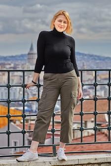 Turysta w stambule jest sfotografowany na tle pejzażu miasta, młoda europejska kobieta uśmiecha się do zdjęcia
