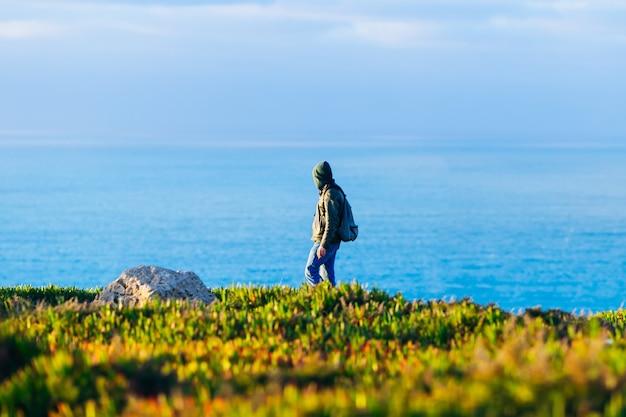 Turysta w zielonym swetrze z kapturem spacerujący po malowniczym brzegu oceanu