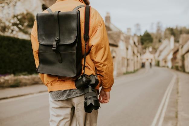 Turysta wchodzący do wioski na widok z tyłu