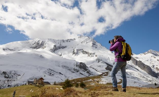 Turysta z aparatem i plecakiem fotografowanie pięknej góry