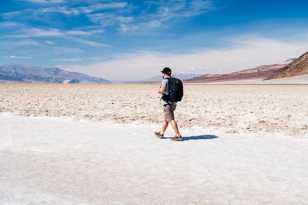 Turysta z czapką chroniącą przed słońcem i plecakiem podróżnika cieszy się słoneczny dzień na pustyni death valley