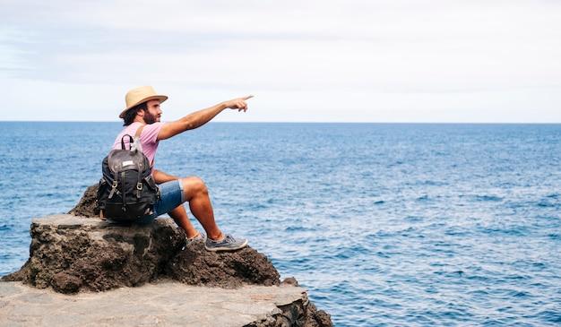 Turysta z czapką i plecakiem na wybrzeżu z morzem w tle.