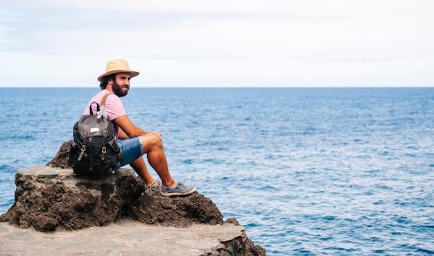 Turysta z czapką i plecakiem na wybrzeżu z morzem