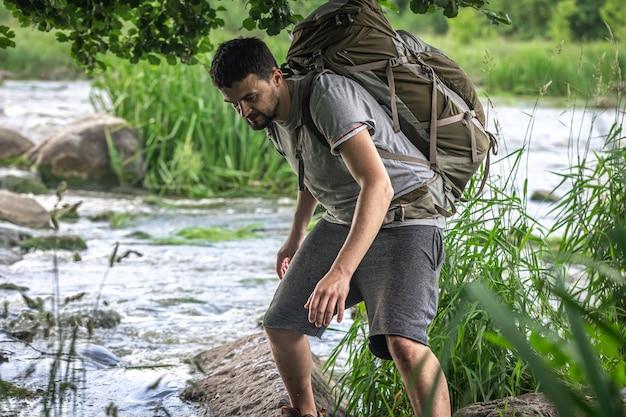 Turysta z dużym plecakiem turystycznym chłodzi się w letnie upały nad górską rzeką.