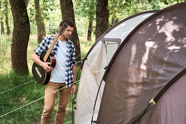 Turysta z gitarą w pobliżu namiotu kempingowego