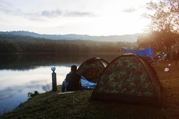 Turysta z obozem namiotowym wzdłuż rzeki.
