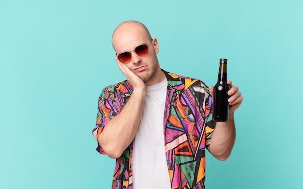 Turysta z piwem turysta czuje się znudzony, sfrustrowany i senny po męczącym, nudnym i żmudnym zadaniu, trzymając twarz ręką