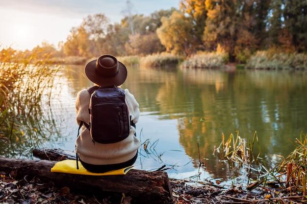 Turysta z plecaka obsiadaniem na brzeg rzeki przy zmierzchem. kobieta w średnim wieku, podziwiając jesień natura