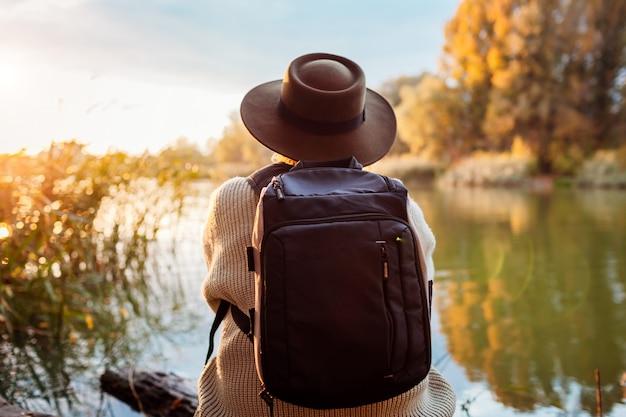 Turysta z plecaka obsiadaniem na brzeg rzeki przy zmierzchem. kobieta w średnim wieku relaksuje i podziwia jesień naturę
